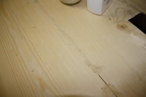 """Spalten zukleben am Sehr Großen Tisch, Experiment mit """"drüberstreuen"""" bei den dicksten Spalten; unten ist der Klebstoff übergelaufen."""